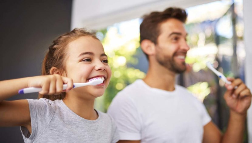 girl brushes her teeth with dad pediatric dentist advice