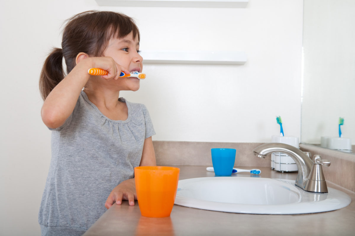 Little girl getting ready in the morning by brushing her teeth.