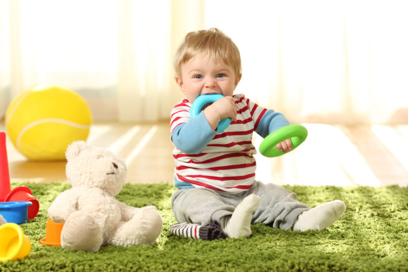 Front view portrait of a happy baby biting toys on a carpet at home.